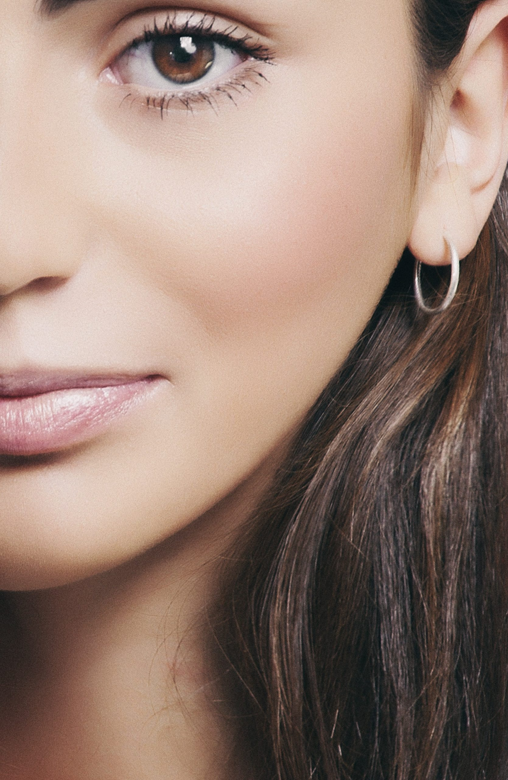 close up of a woman wearing natural makeup, a light lipstick, giving the appearance of plump lips.