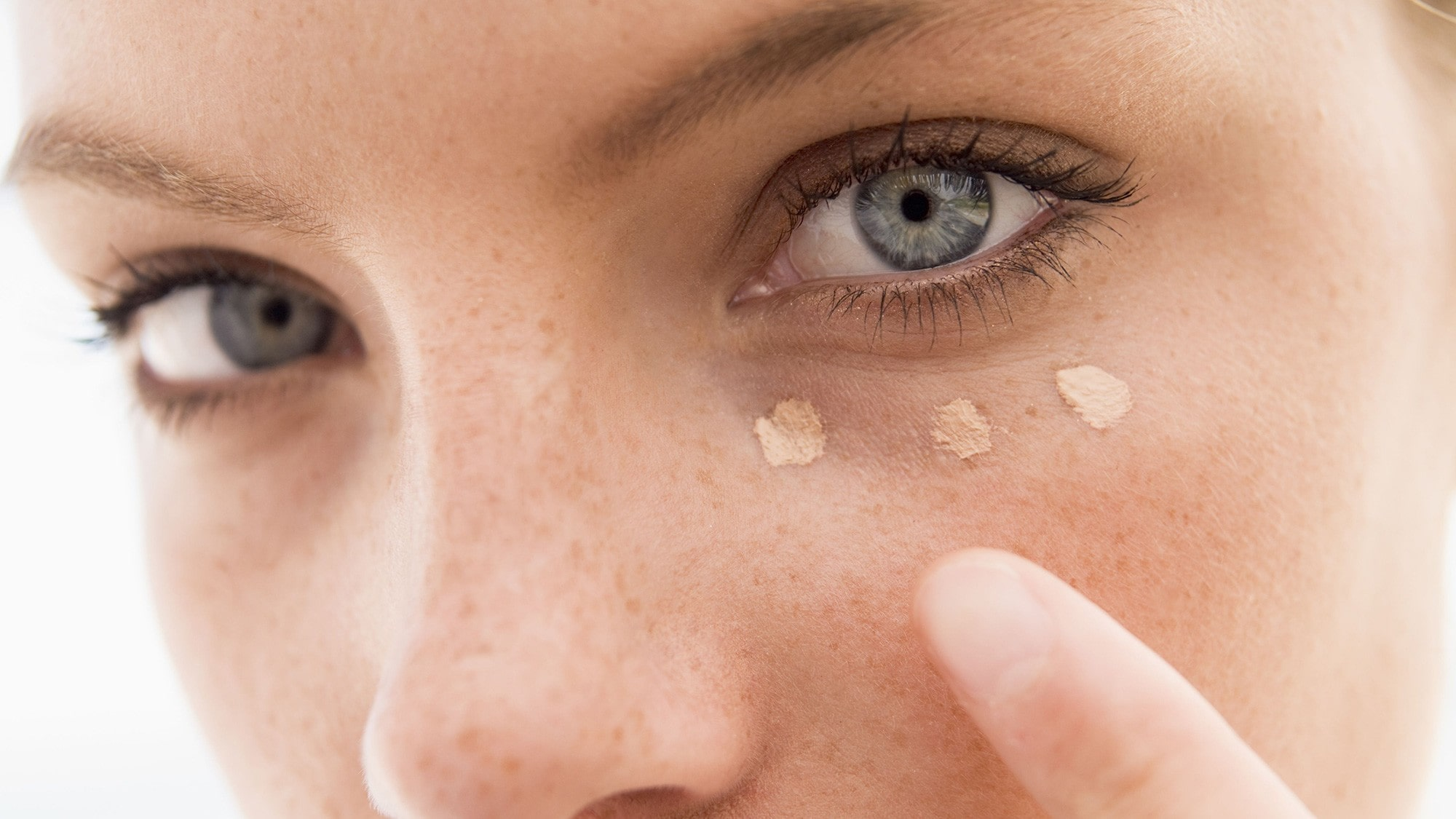 closeup of woman applying concealer to her under-eye area.
