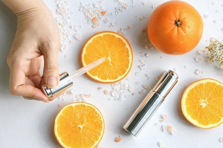 close up of a hand using a dropper onto a slice of orange.