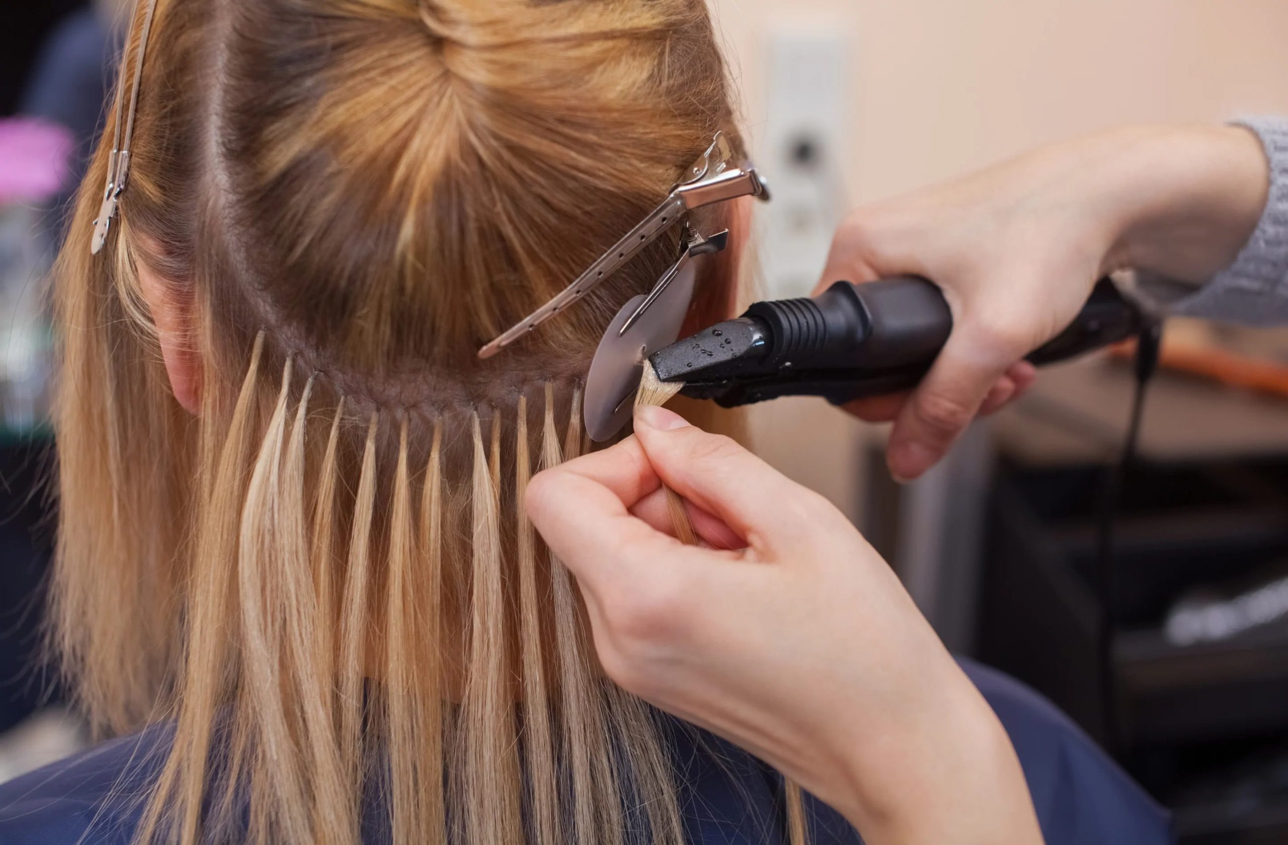 close up of a person having glue-in extensions applied.