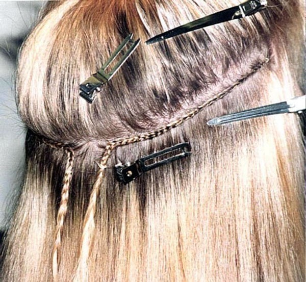 close up of a person having sew in extensions.