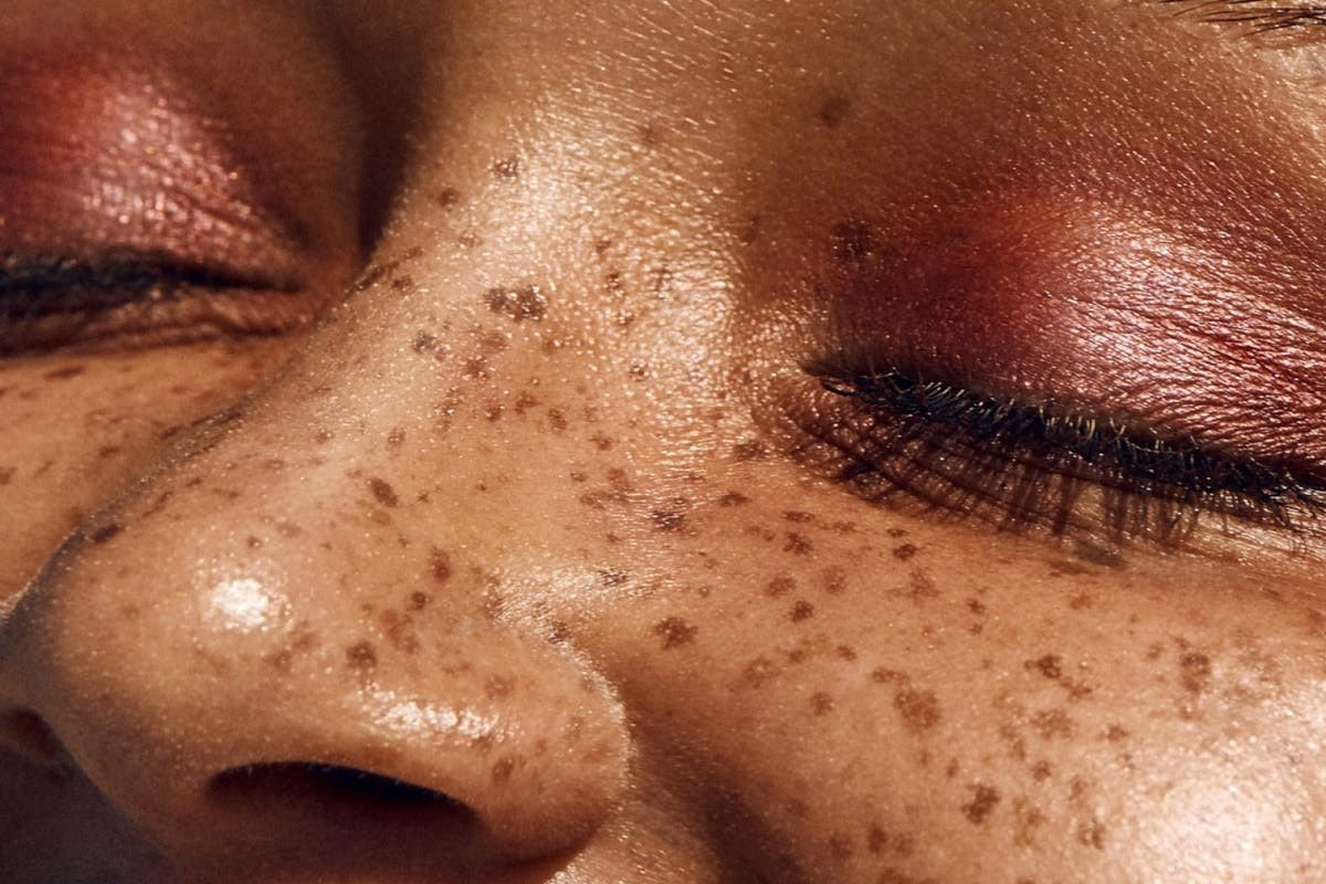 close up of woman's face, wearing pink eyeshadow with freckles over her nose and cheek.