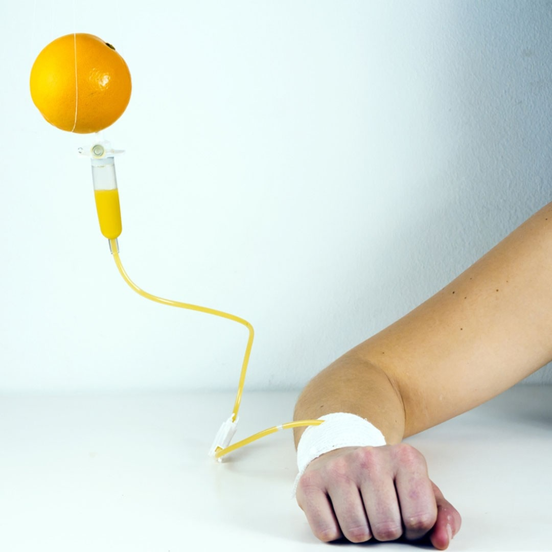 orange dangling next to a drip, attached within a persons arm.