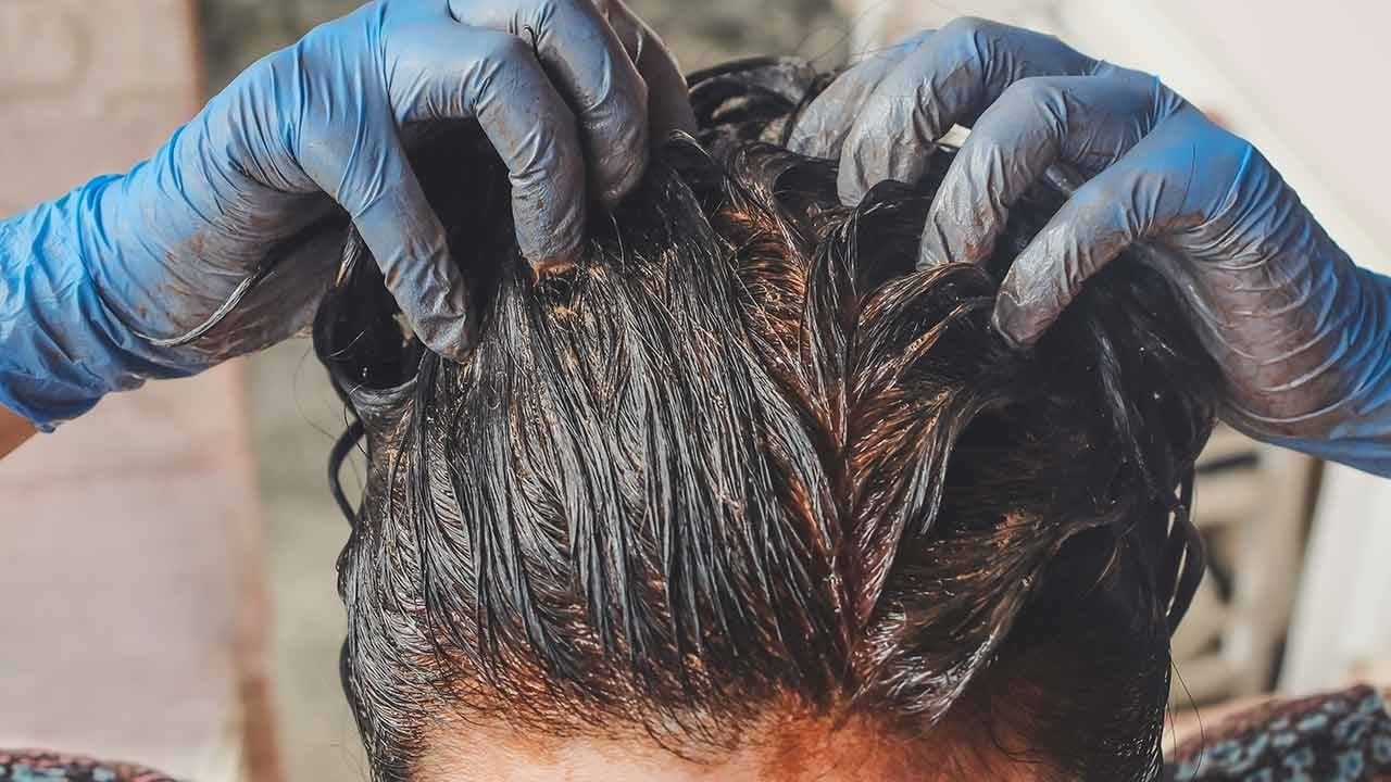 person applying henna dye to their hair whilst wearing protective gloves.