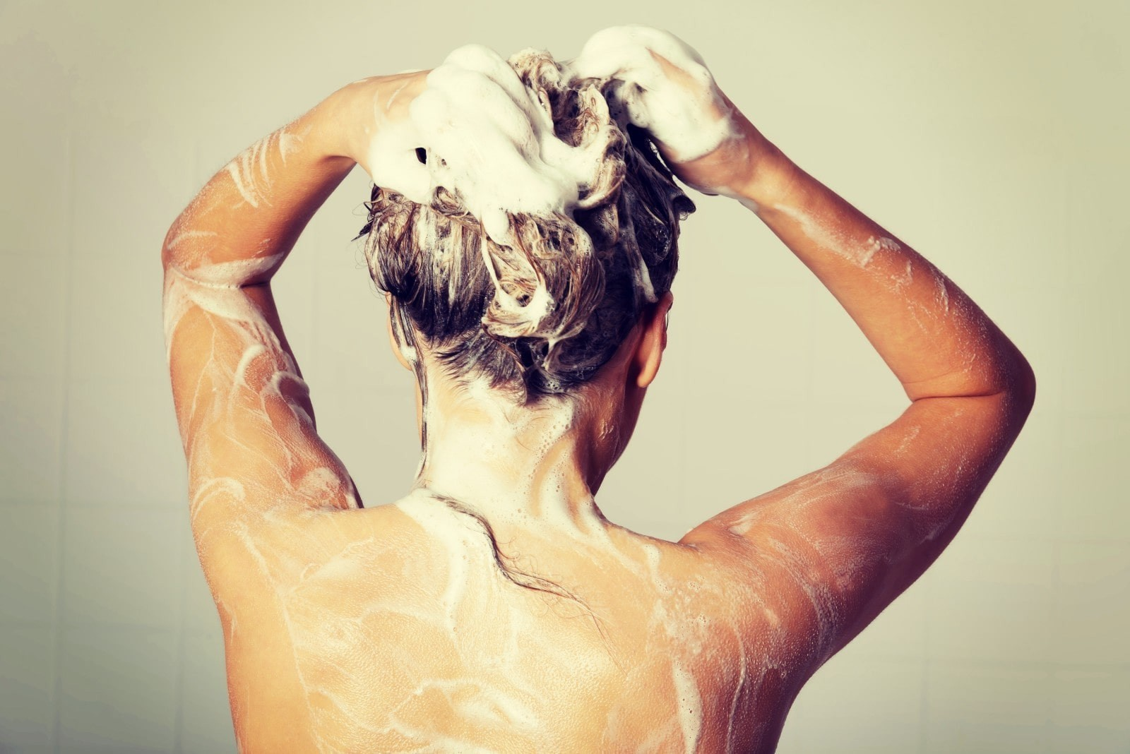 person pictured from behind cleaning their hair, with soap suds.