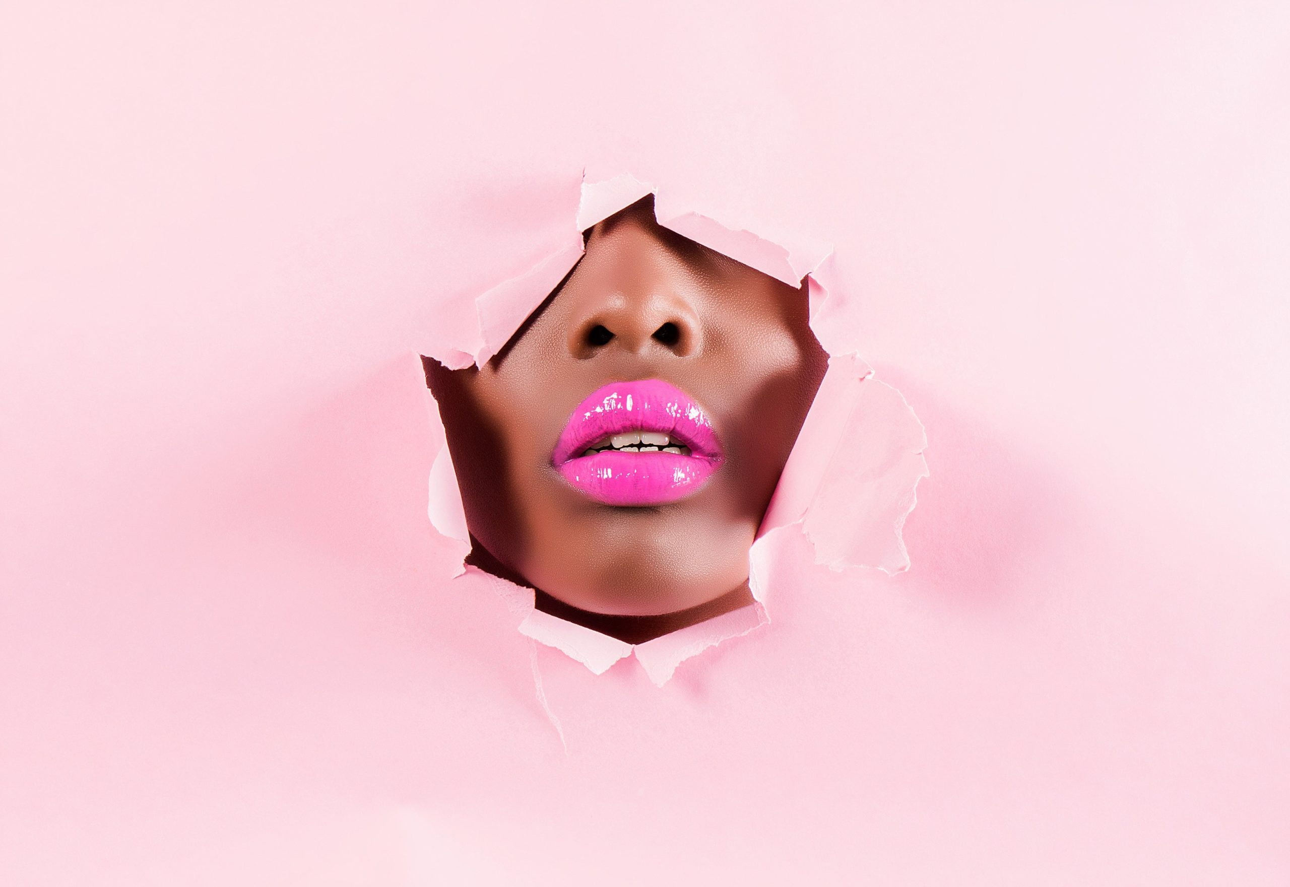 full image is pink, but a hole cut in the middle, separating the paper, of which a woman is posing with pink lips close up.
