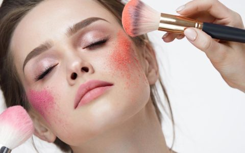 pink orange powder displayed on models cheeks.