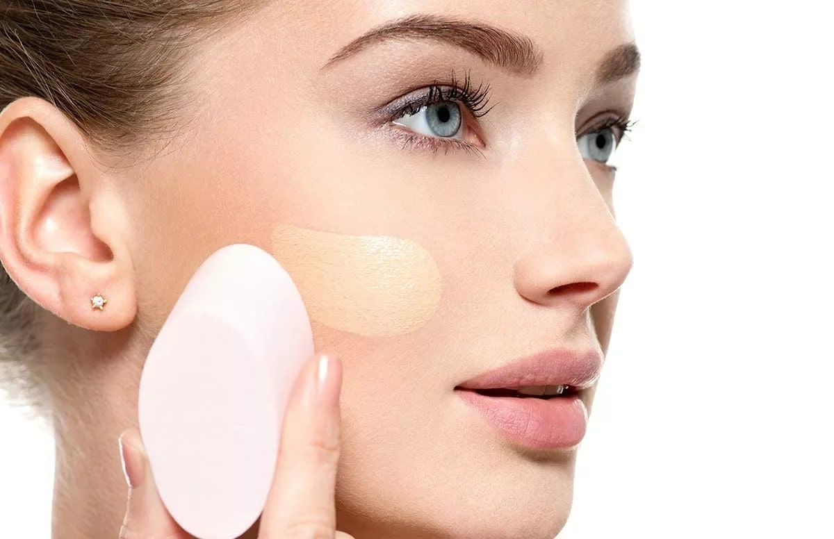 woman applying foundation with a sponge.
