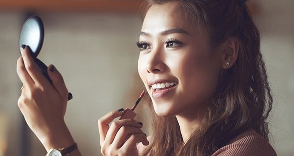 woman applying lip gloss whilst smiling into a compact mirror.