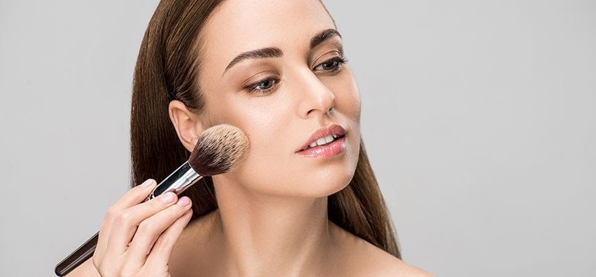 woman applying powder foundation to her face.