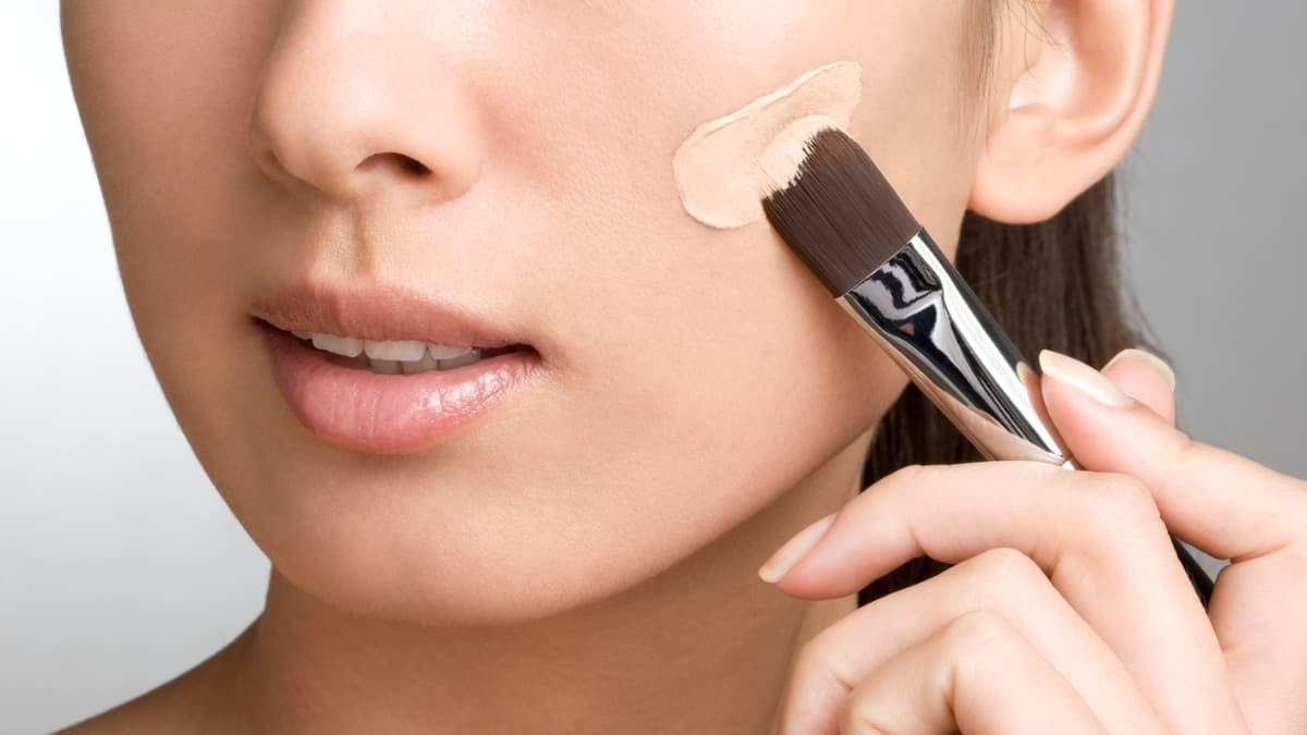 close up picture of a woman applying foundation with a brush, on her cheek.
