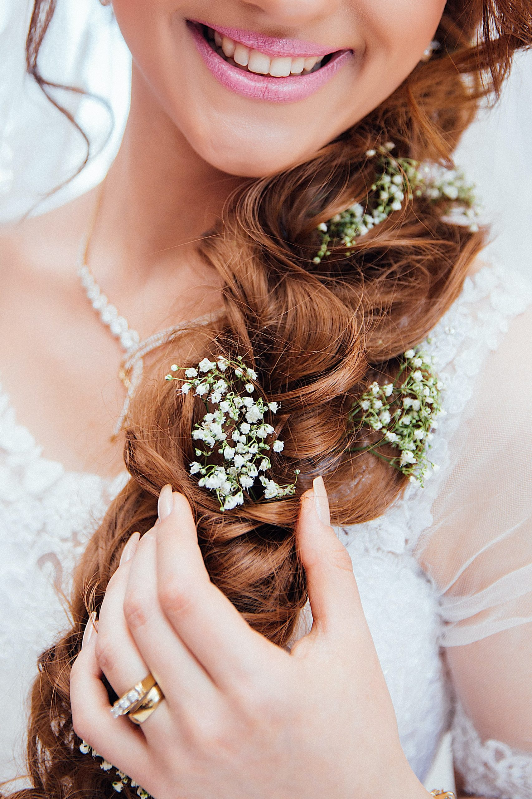 woman dressed for wedding with plaited hair and pink lips.