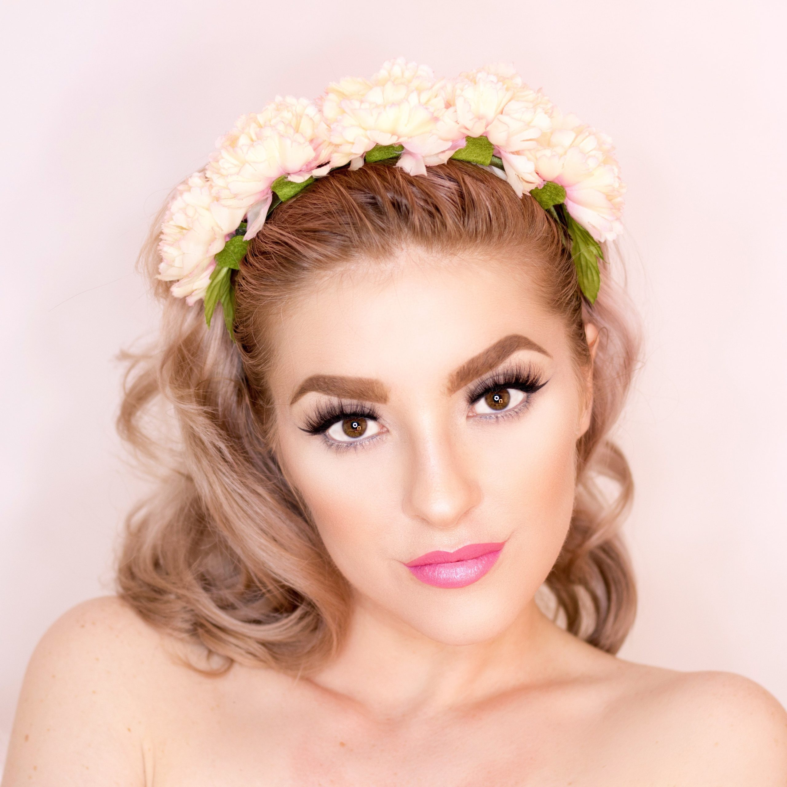 woman wearing pink lipstick with flowers around her hair, like crown.
