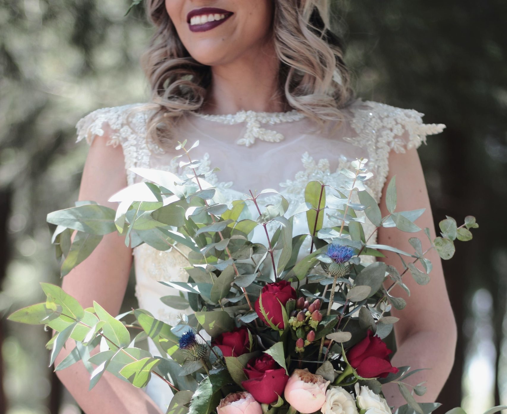 woman in wedding dress, holding flowers and wearing dark lipstick.