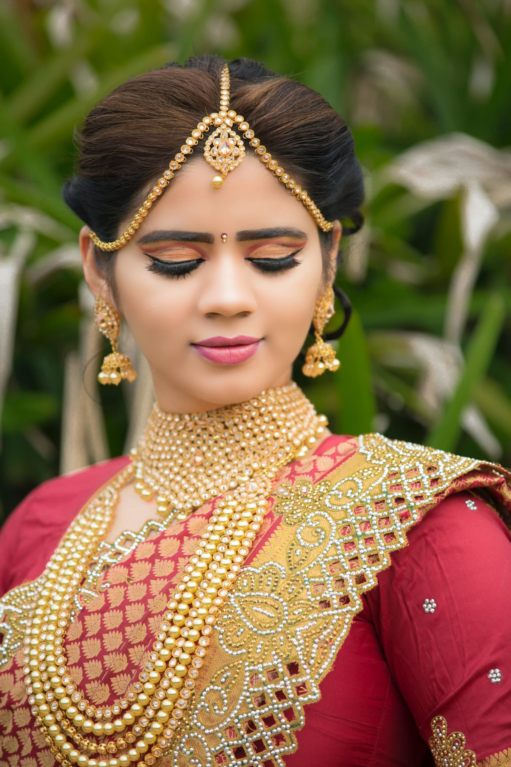 woman looking downwards, whilst wearing traditional bridal clothing.
