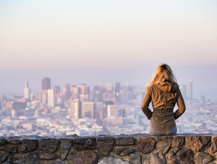 woman pictured from behind, sat on a wall facing out to a city landscape, viewing sunrise fog and possible pollution.