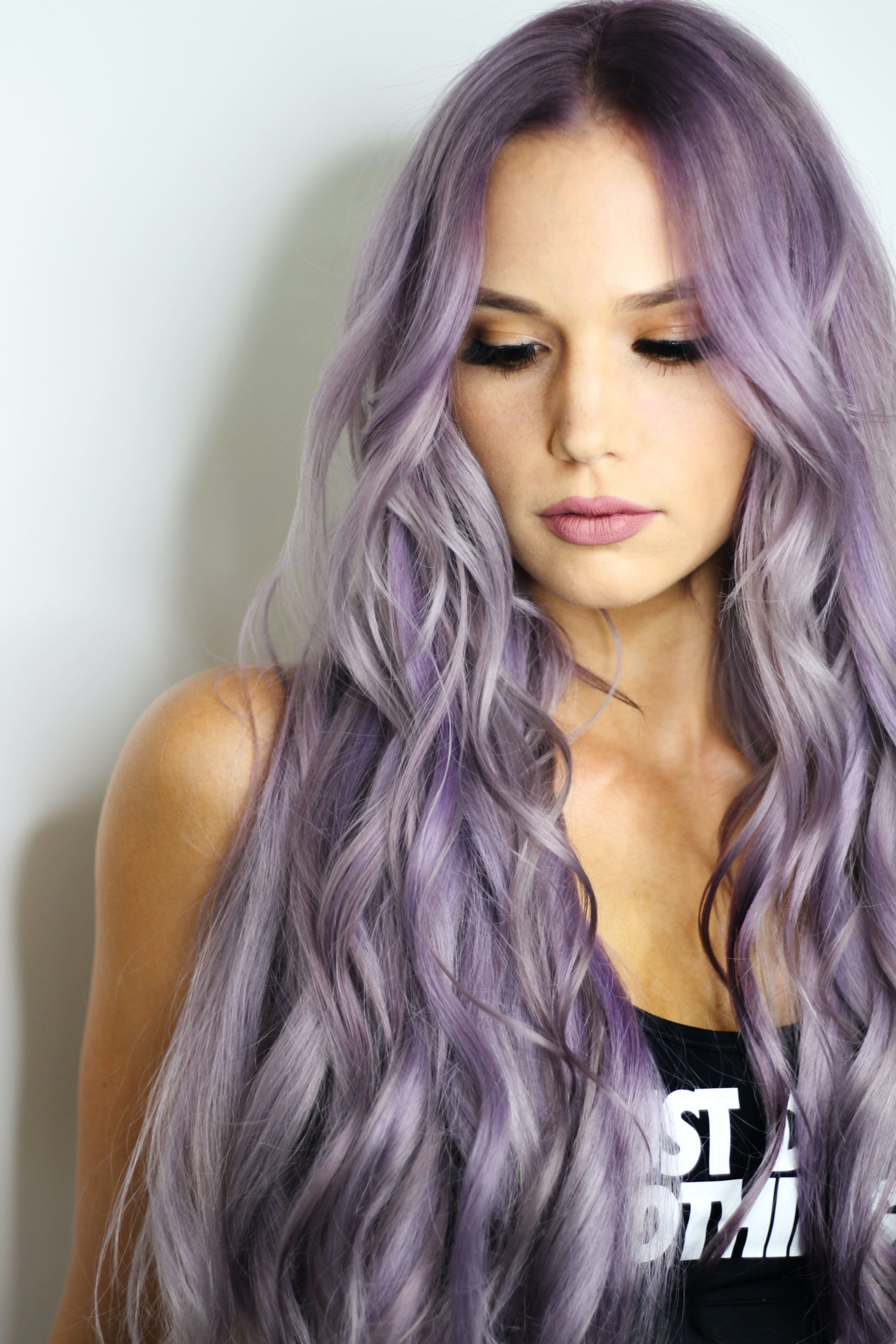 woman pictured with long hair dyed a colourful lilac purple.