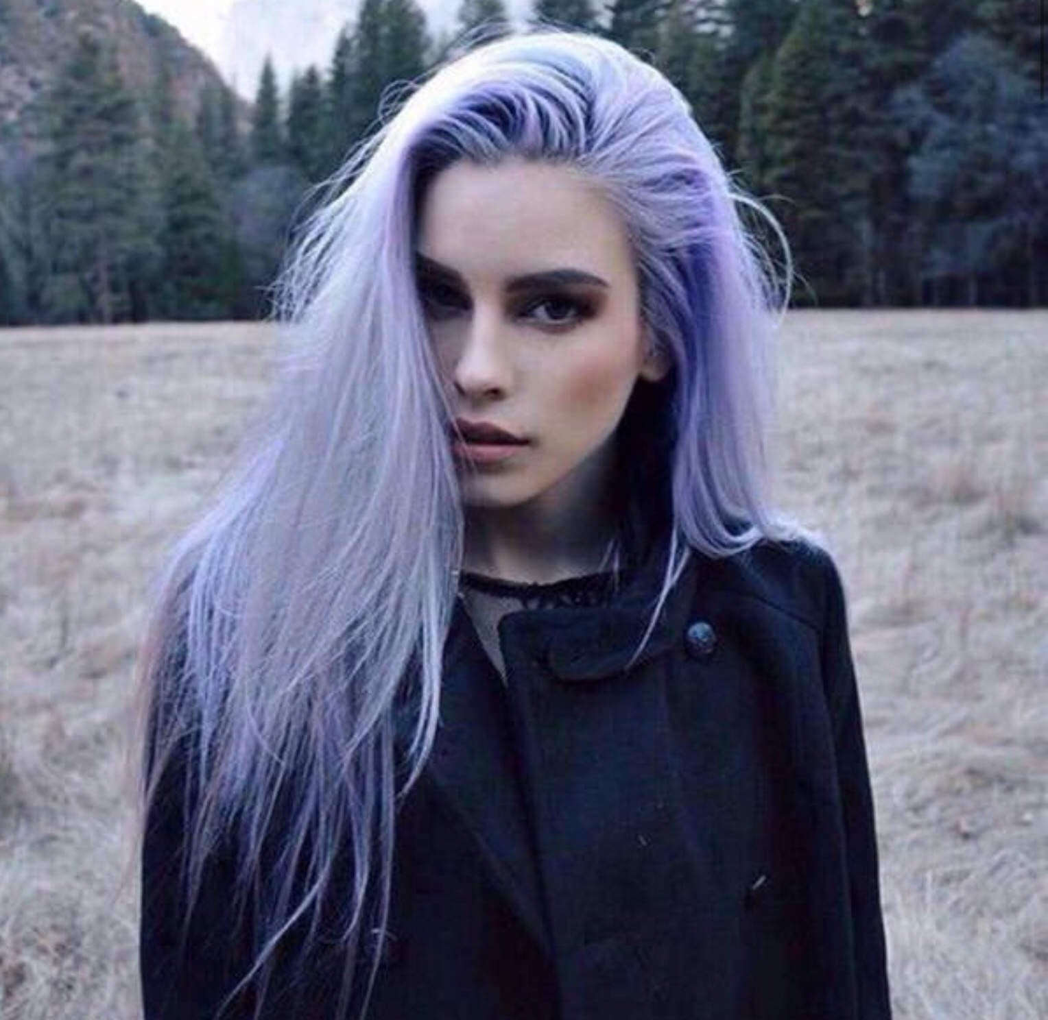 woman stood in a field with ice blue hair.