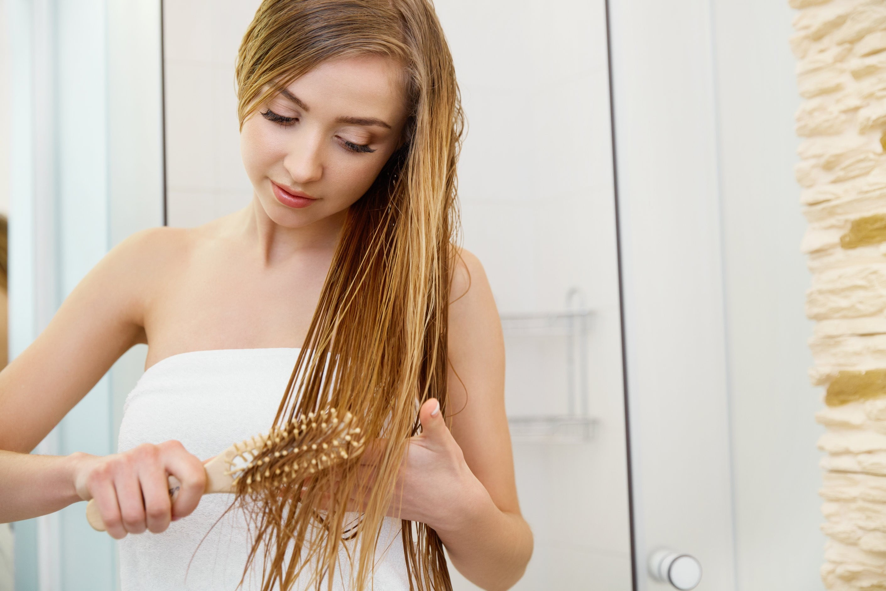 woman wearing a white towel, whilst brushing her wet hair.