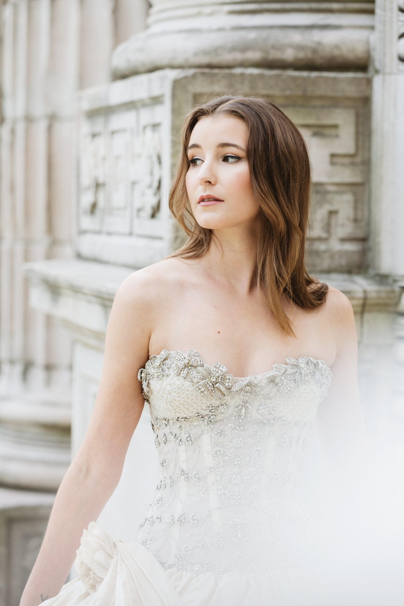woman with calm, collected wedding makeup, wearing a wedding dress against an old building.