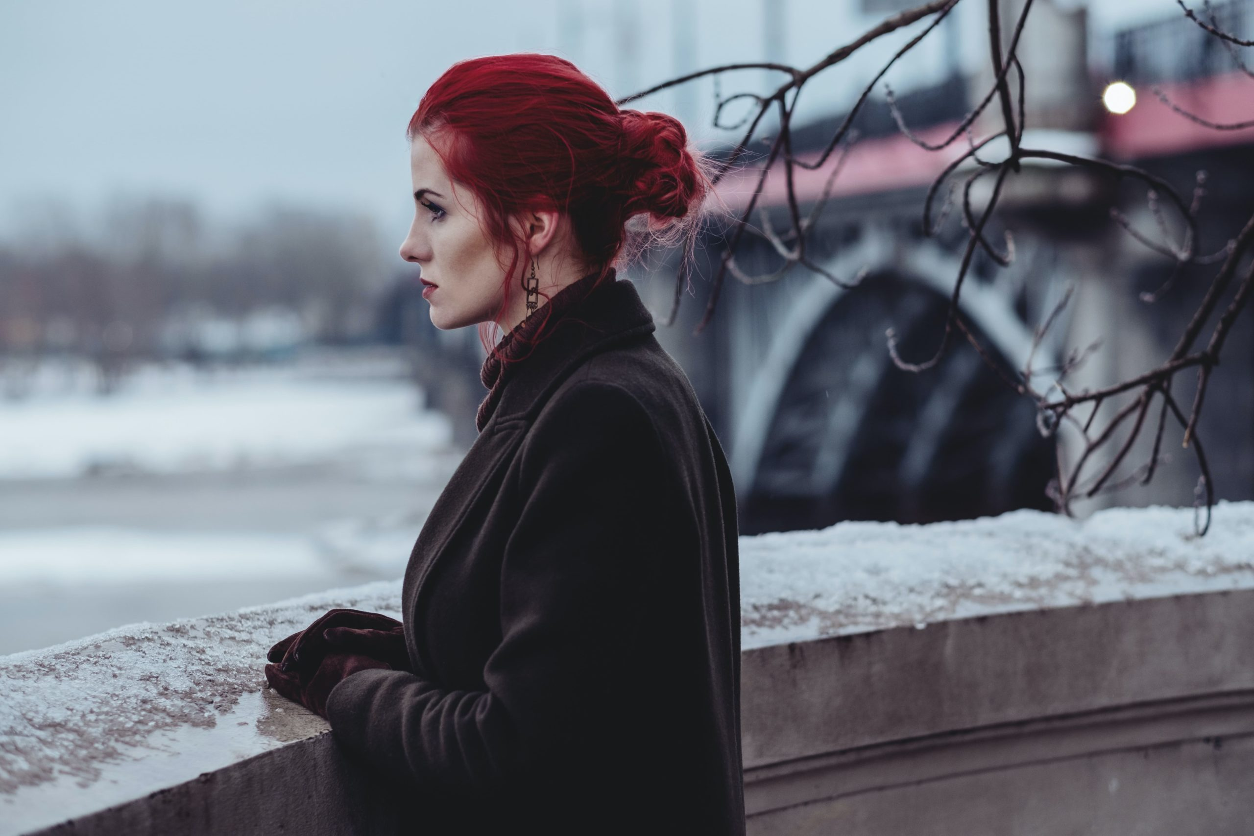 woman with dyed colourful red hair, looks over a wall into water, with a bridge behind her.