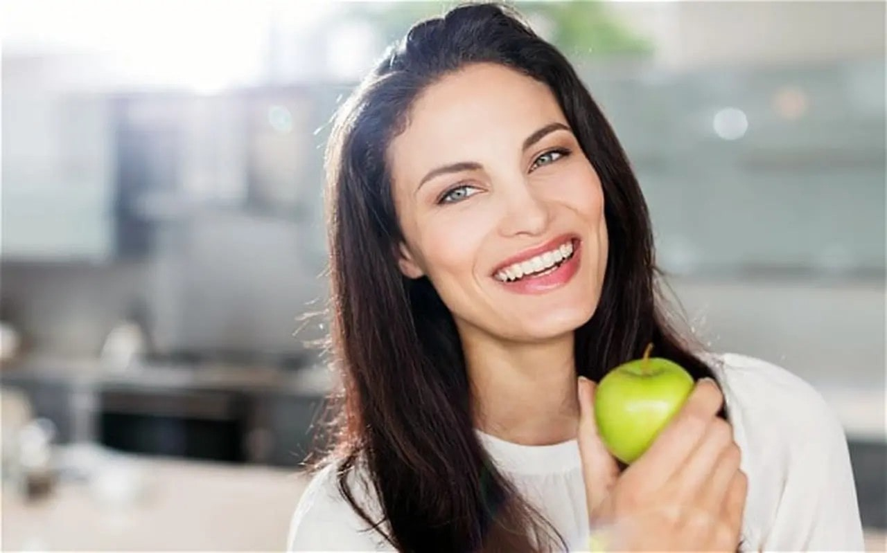 a woman smiling, as she holds a green apple.