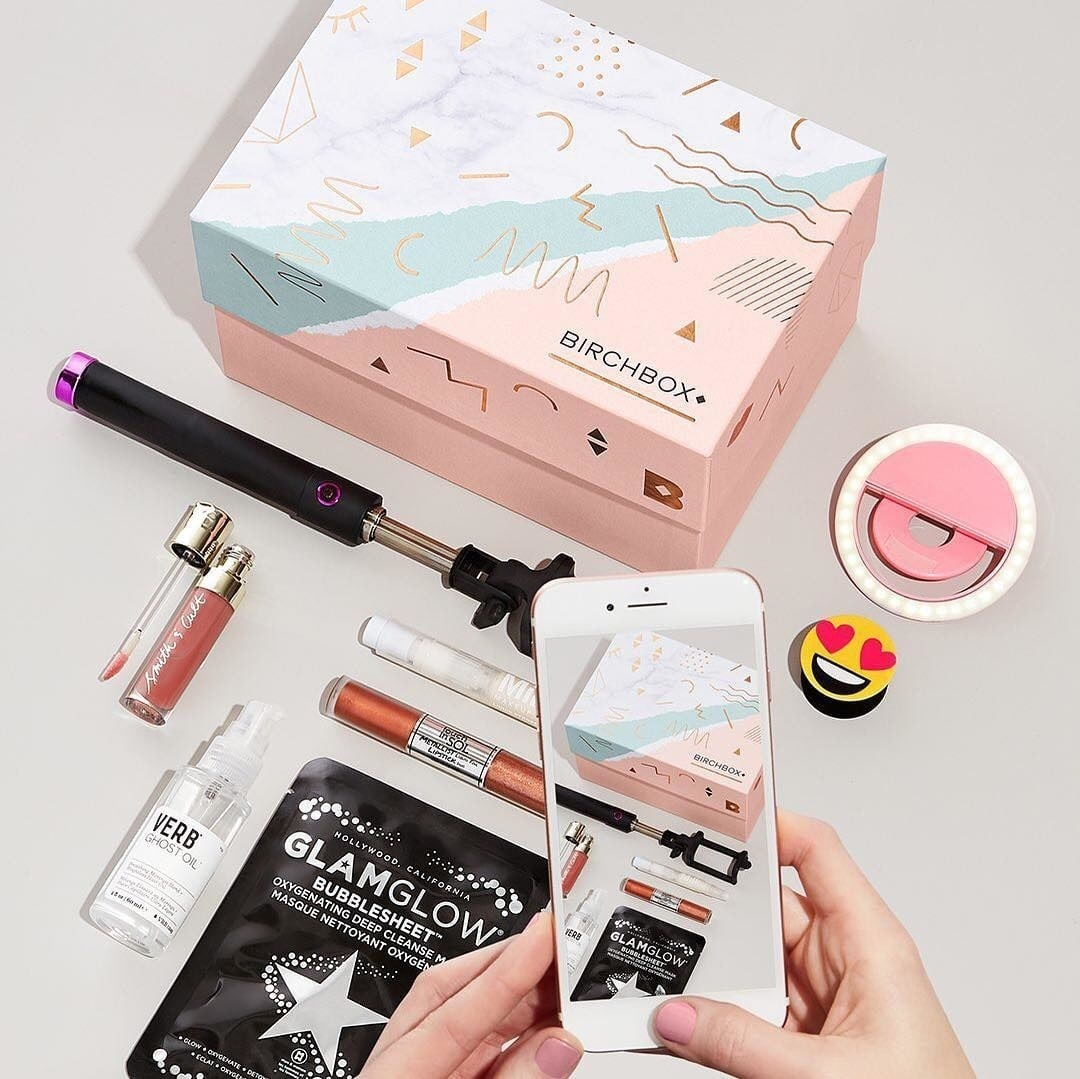 Beauty subscription boxes: BirchBox Beauty Subscription gift box with cosmetic products surrounding it.