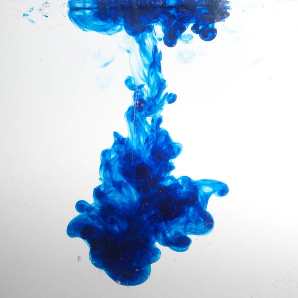 blue ink/dye floating in clear fluid.