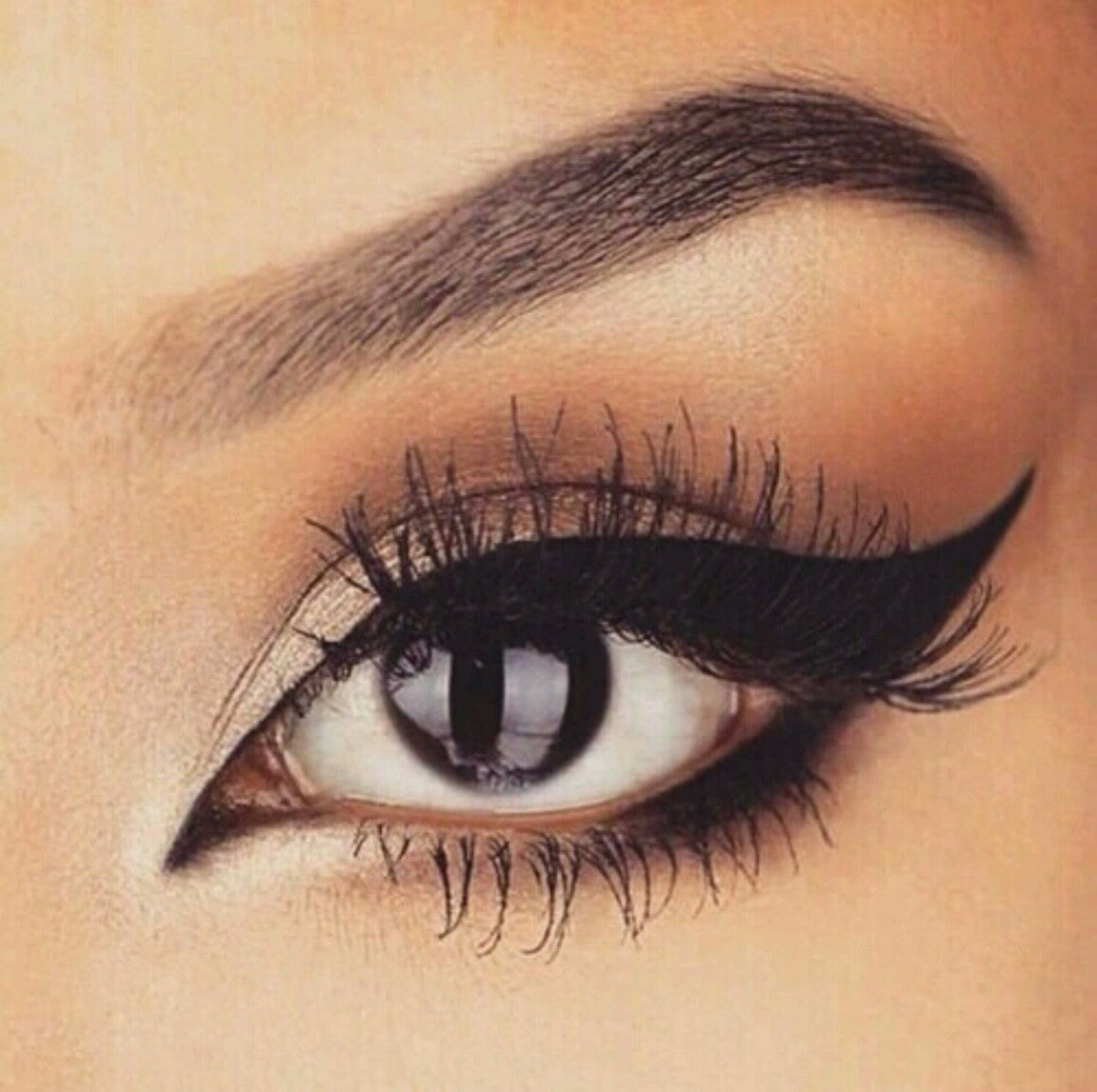 close up of a womans' eyeliner, perfectly winged with dark eyes.