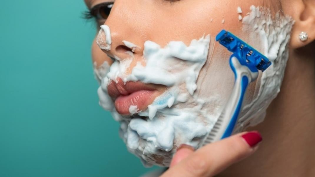 close up of a woman shaving her face with cream and a razor.