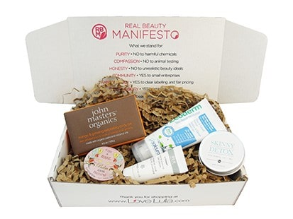 lovelula manifesto real beauty box with various cosmetic products within it, on top of tissue paper.