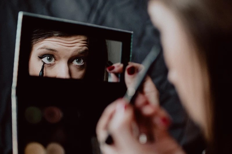 woman applying eyeliner whilst using a compact.