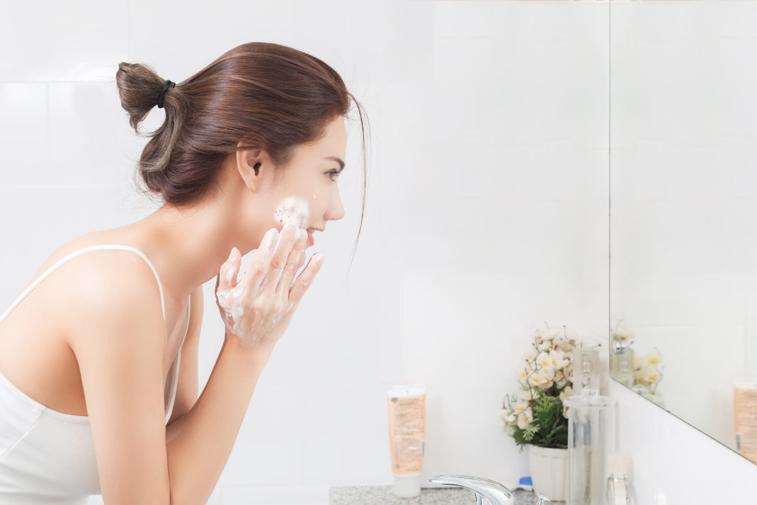 woman applying her skincare at night time.