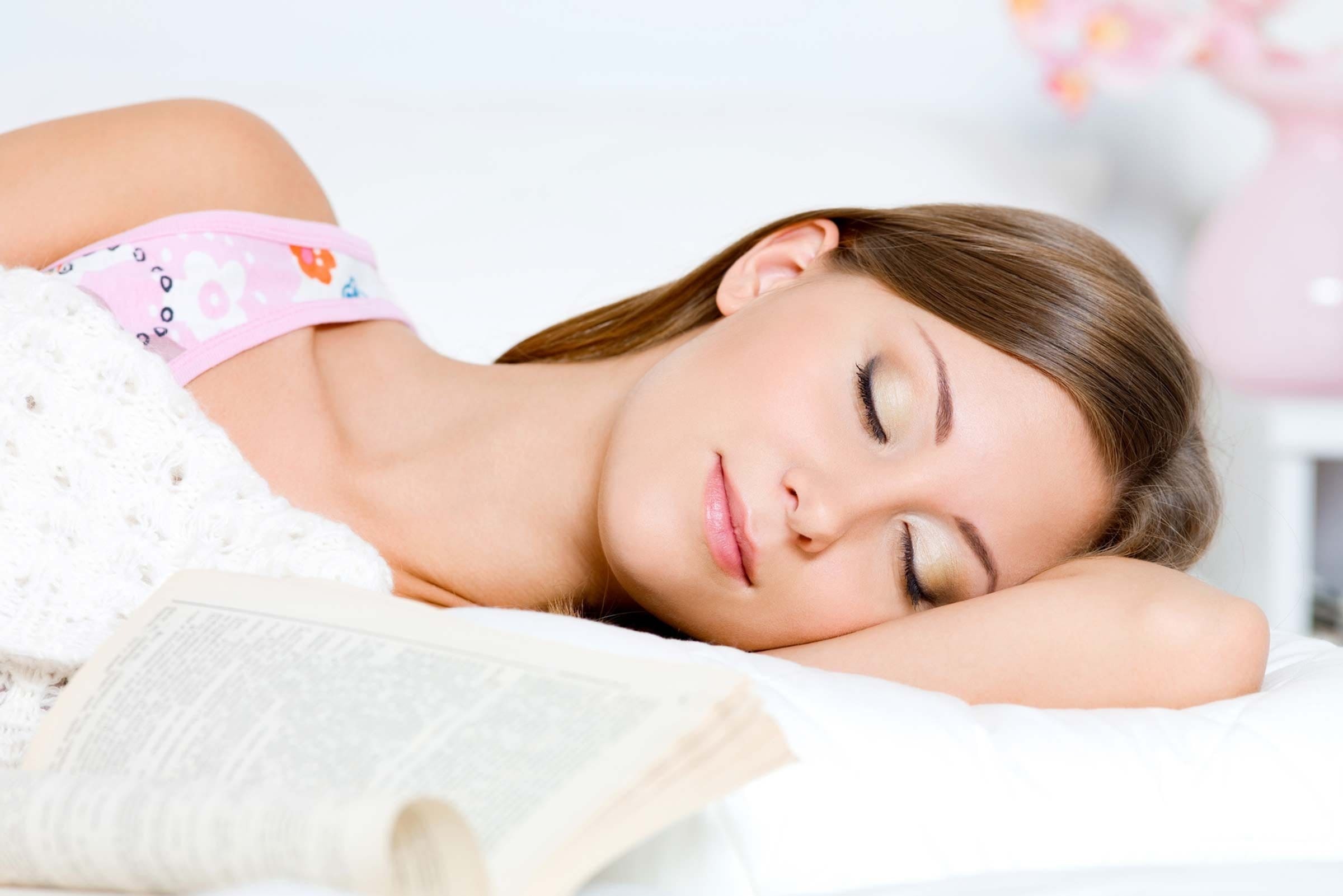 woman asleep, with a book by her side, wearing a full face of makeup.