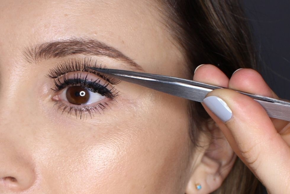 a close up of a woman applying eyelash extensions.