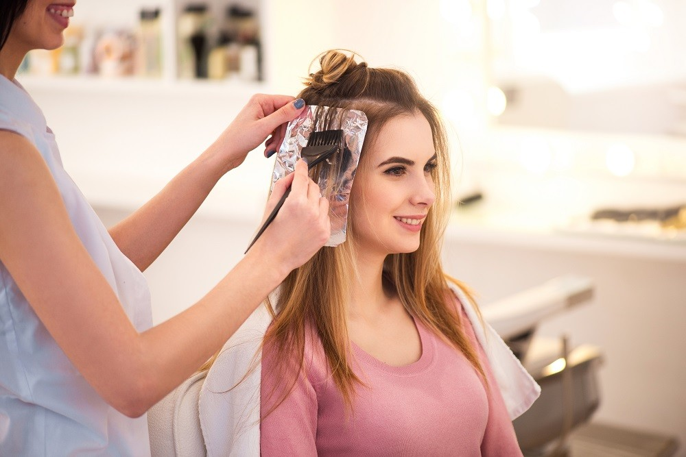 Brassy Hair Avoidance: woman having her hair dyed, with foils, professionally.