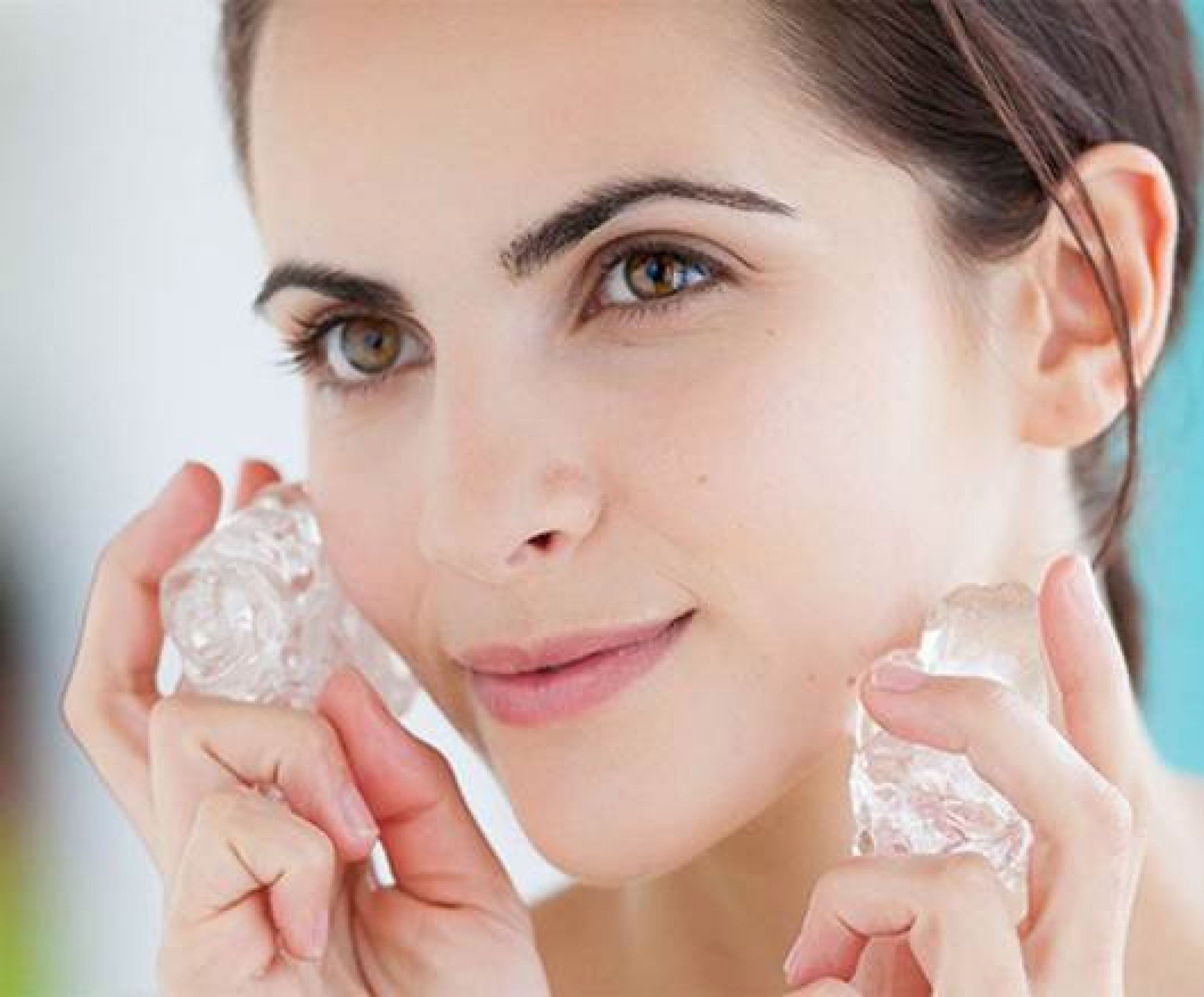skin icing: woman smiling and holding ice cubes against her face.