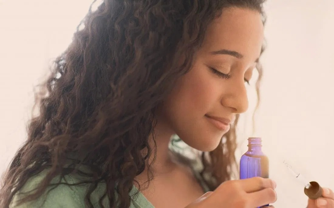 woman smelling from a glass bottle, holding a dropler.