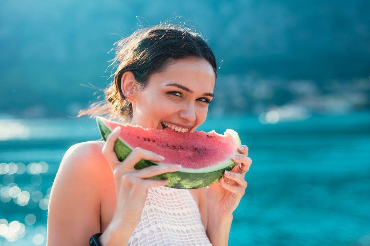 woman smiling as she bites into a watermelon slice.