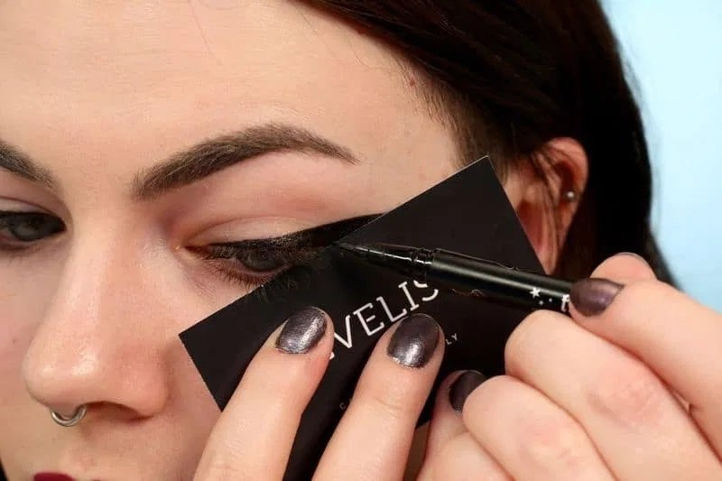 woman using a business card to apply her eyeliner, as a stencil.