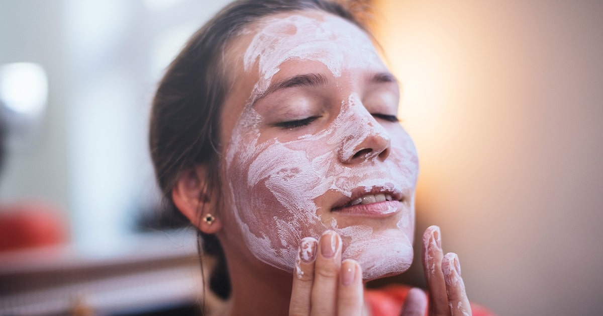 woman using calamline lotion on her face.