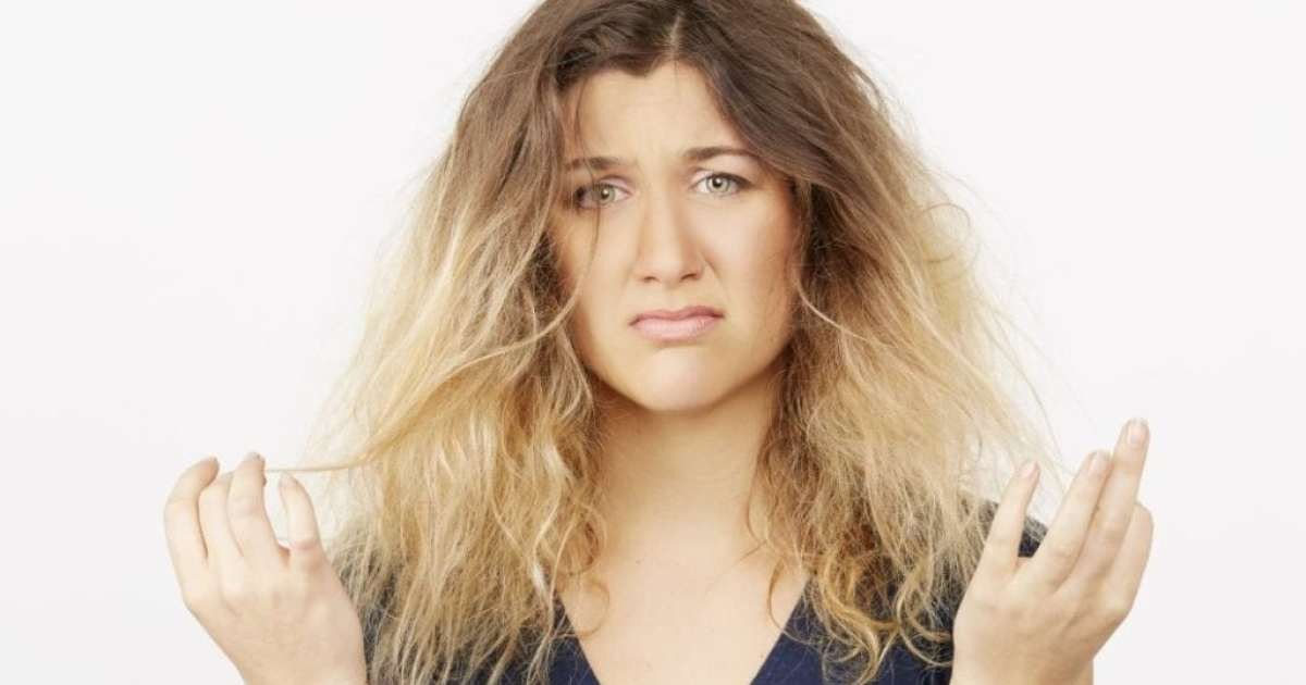 woman with blonde/brown dyed frizzy hair, looking unhappy.