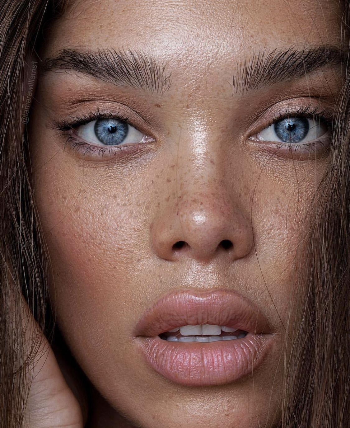 womans face close up, tanned, radiant with blue eyes.