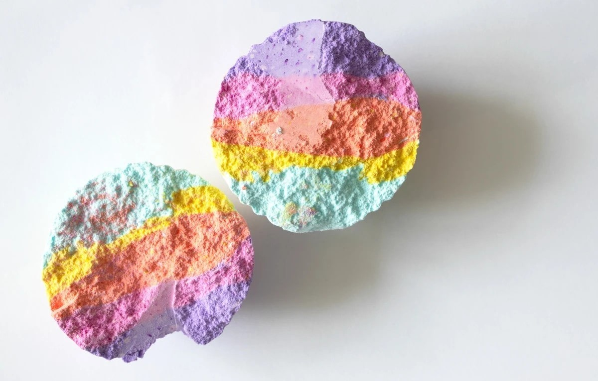 a halved rainbow-coloured bath bomb.