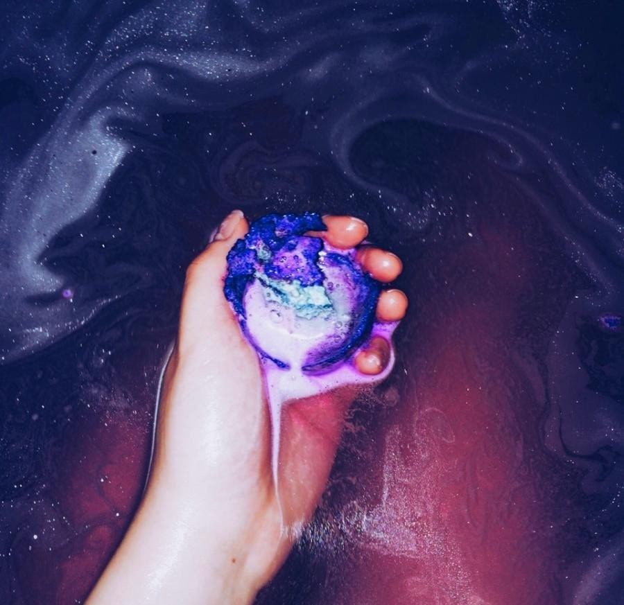a hand holding a bath sparkly bomb under water.