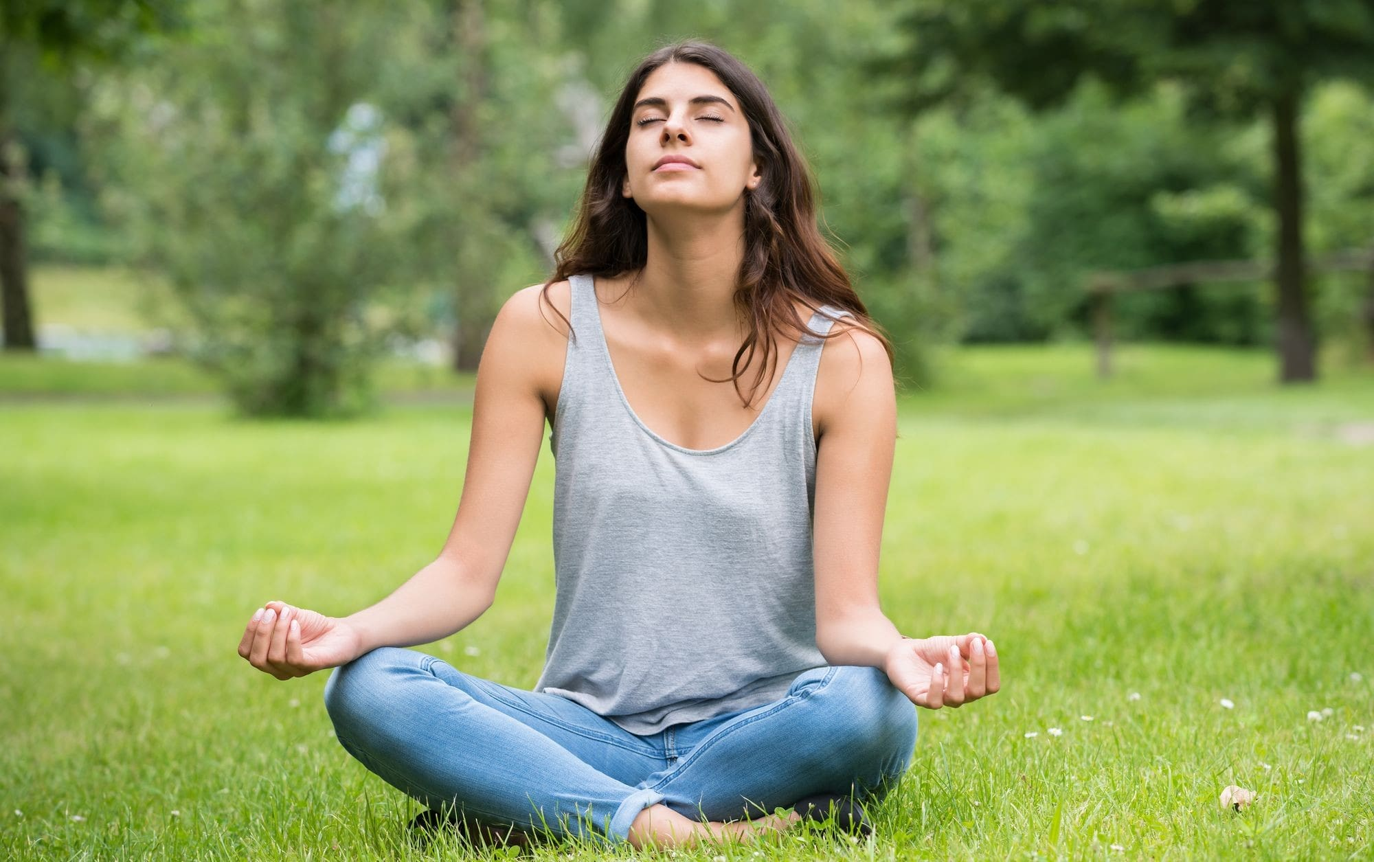 a woman sat crossed legged on grass, meditating, relieving stress, with her eyes closed.