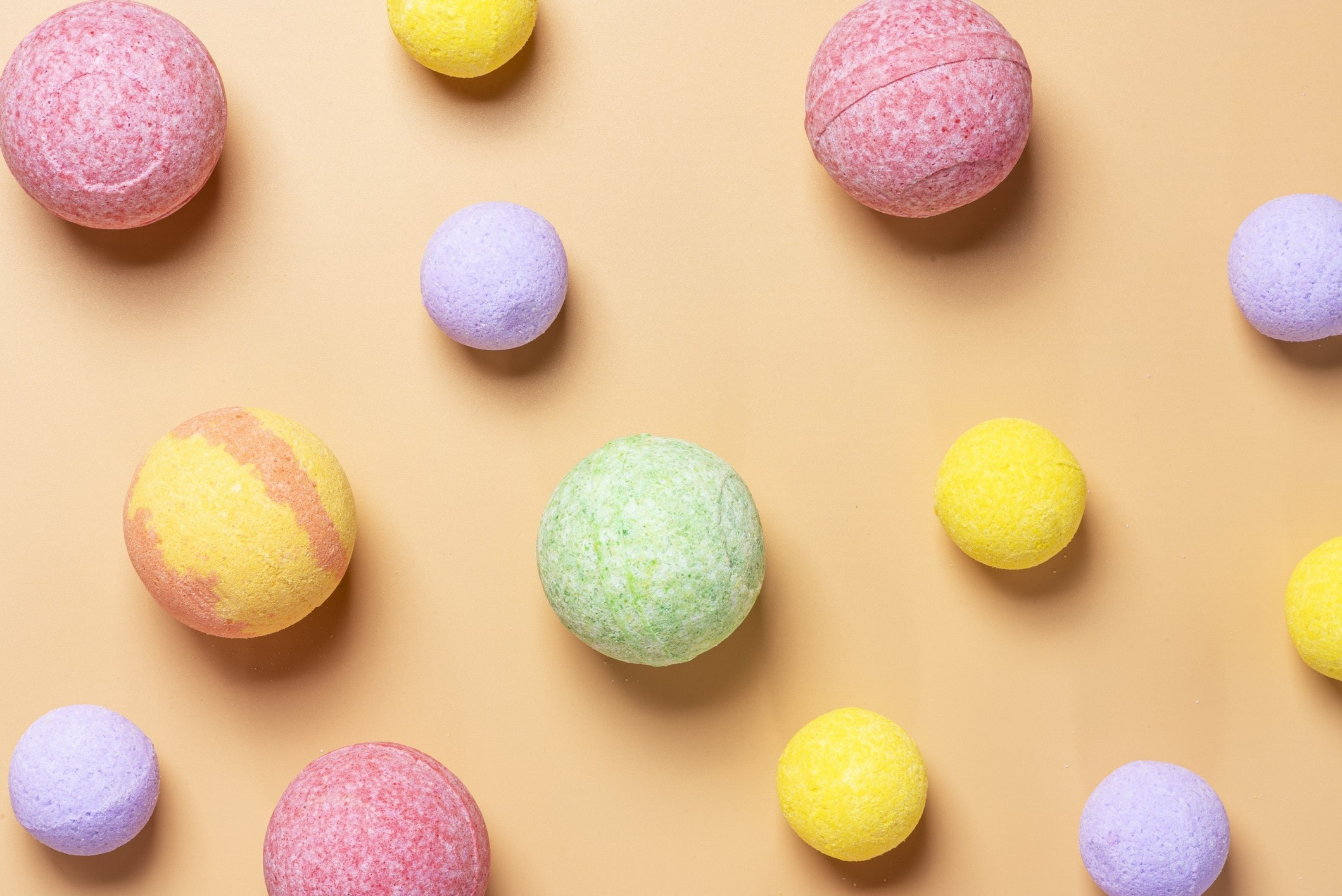 an array of different coloured bath bombs on a peachy background.