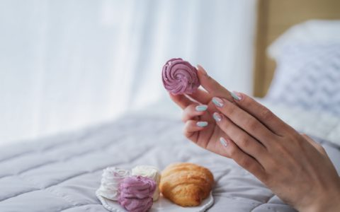 close up of hands with painted nails, holding pastel coloured macarons.