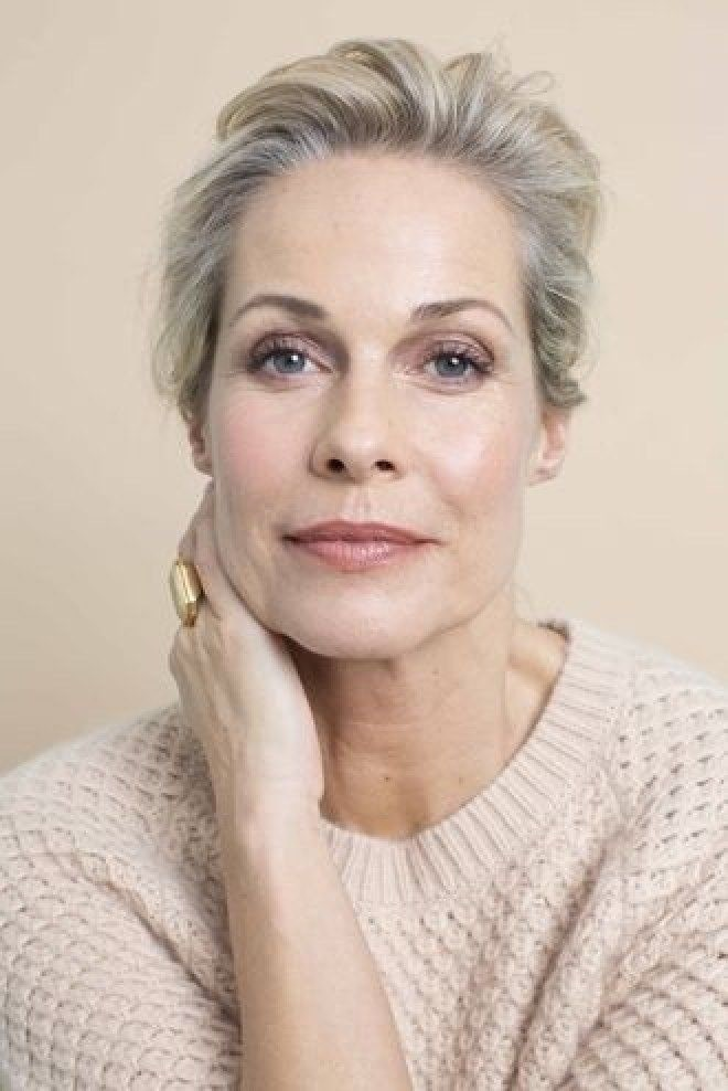 mature woman with her hair tied up, whilst wearing a wool jumper.