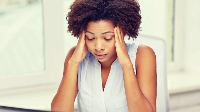 Stress: Woman with her hands at either side of her head.